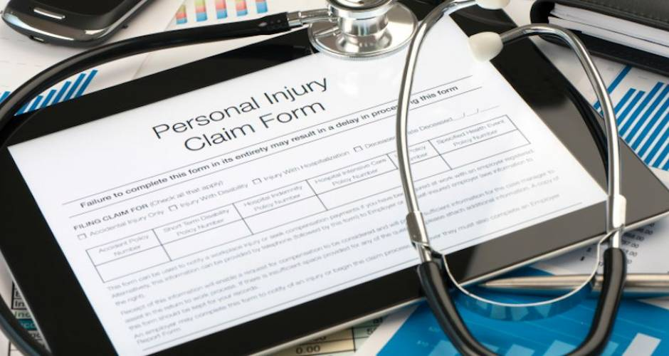 Personal injury form on a digital tablet with stethoscope and paperwork